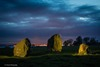 The three boulders at night with the lights of Grangemouth and Bo'ness on the horizon
