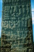 This lower-central panel shows, at top left, seven decapitatied bodieswith their executioner.  To the right are three figures who seem to be blowing instruments - perhaps carnyx, or battle-trumpets.  At top centre is a representation of perhaps a bell (is that a clapper below the notch?) or maybe a broch.