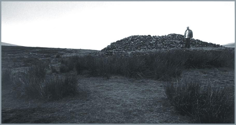 The cairn, looking southwest.  The yardstick is five feet nine inches tall and is standing on an area levelled by robbing about half way up the height of the cairn.
