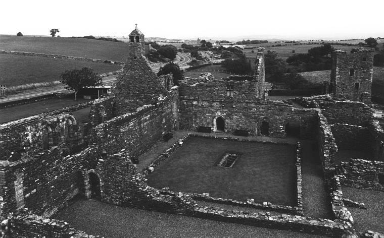 Looking east over the abbey from the gatehouse.  The rectangular well can be seen in the centre of the cloister.  To the left of the cloister is the church.  In the wall at the far side of the cloister can be seen (from the left) the entrance to the chapter house, the entrance to the treasury, and a passageway leading through to the inner court.  To the right of the cloister can be seen the kitchen and dining room.  Beyond these, at the top right of the picture, is the towerhouse.