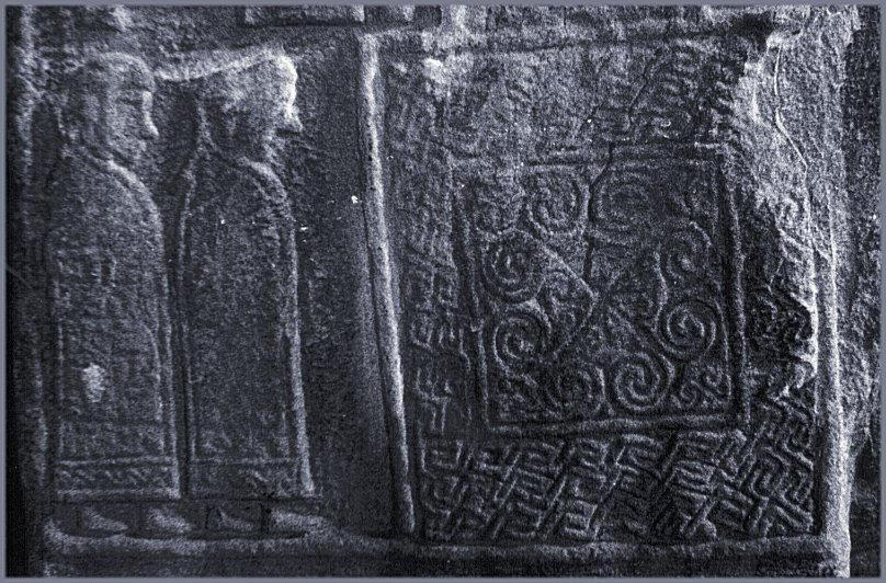 A pair of tonsured monks and a key-pattern panel.