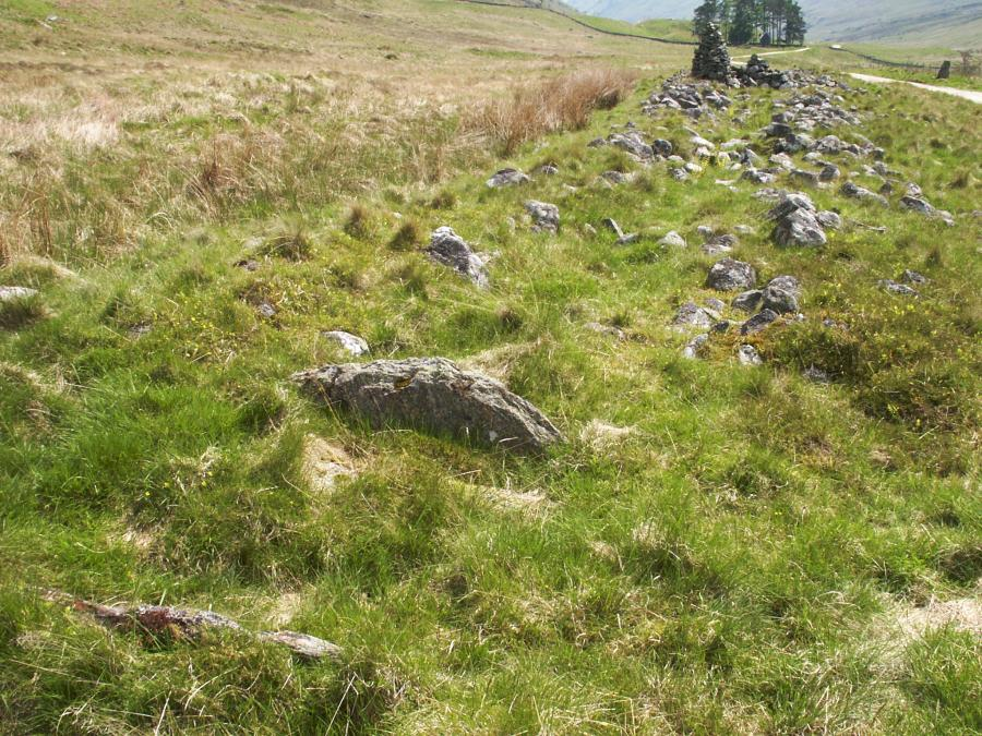 A cist in the centre of the cairn is in the foreground.  The standing stone is in the top-right of the picture.
