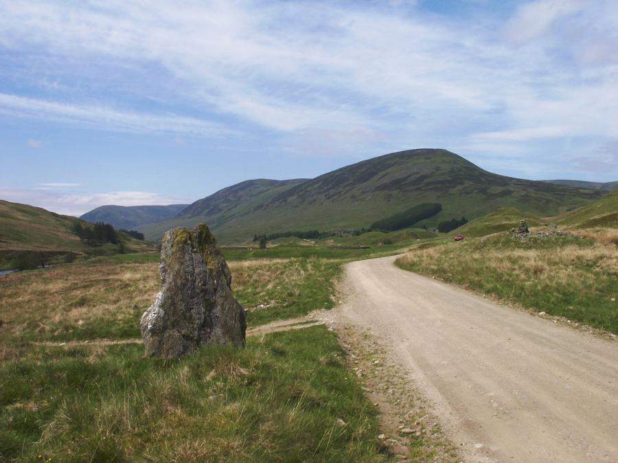 The standing stone, looking northeast along Glen Almond.  The cairn can be seen on the right where the road bends away.