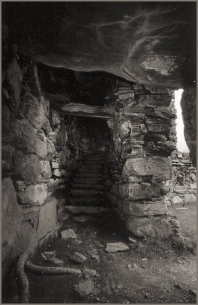 Inside the wall space; the broch courtyard through the entrance on the right and steps leading up ahead