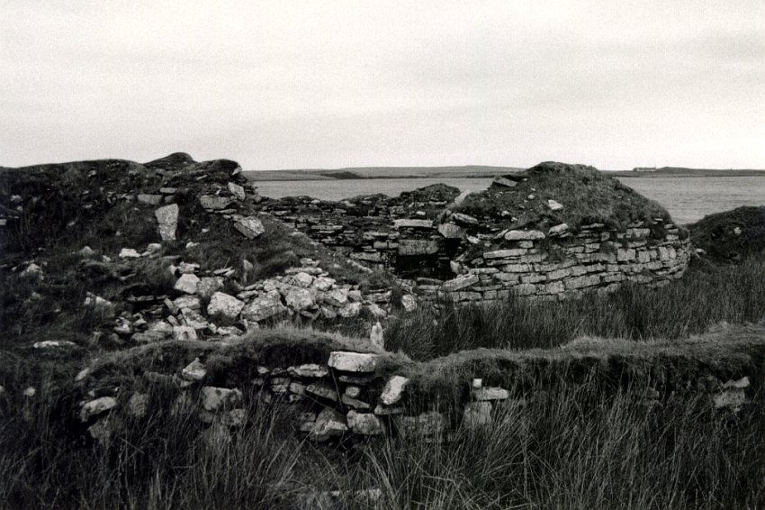 Looking north from the outbuildings.  There is much rubble to the left but a good line of wall curving away to the right.  The Loch of Yarrows is behind.