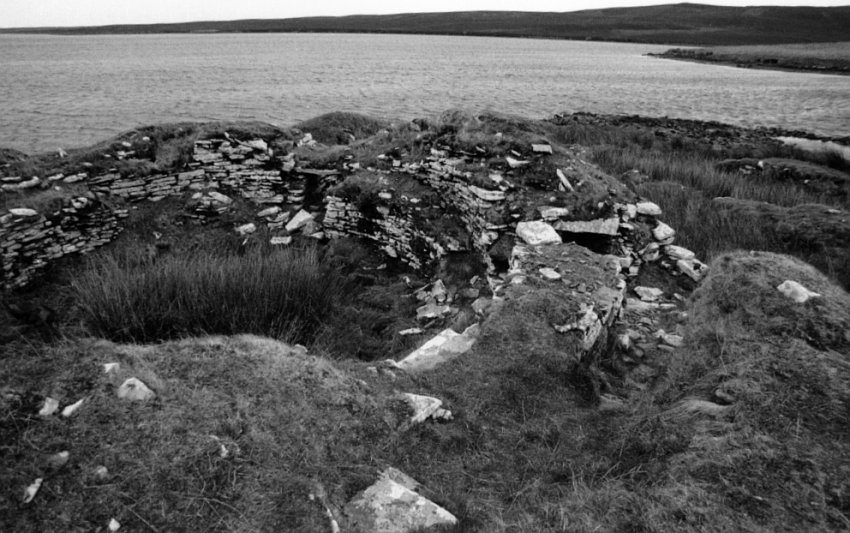 Looking northeast into the body of the broch.  The double-wall can be seen in the lower right.  A large space, suitable for storage, is in the wall cavity below stone covers immediately below my feet.