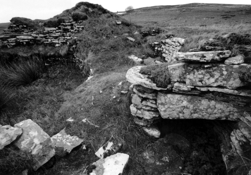 The broch wall.  To the left is the body of the broch.  Bottom right is a large void between the double walls, capped by large flat stones.